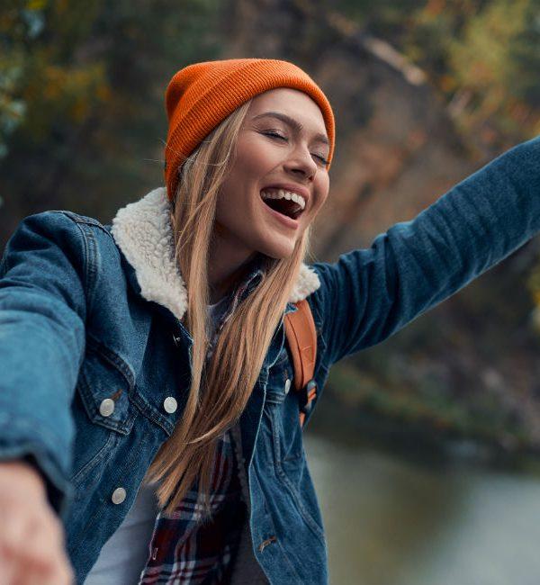 Una ragazza sorridente in un paesaggio montano con lago