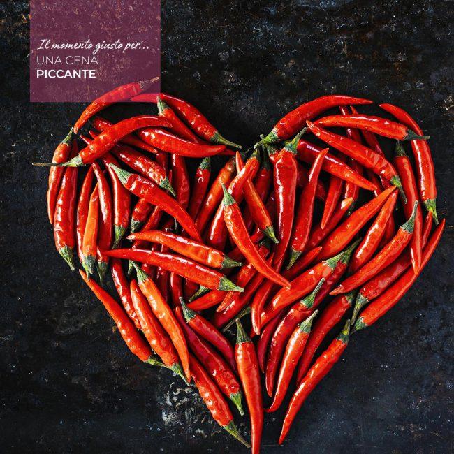 cuore fatto con peperoncini rossi su piano in pietra antracite, scritta
