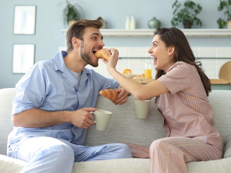 Coppia di conviventi fa colazione sul divano ridendo