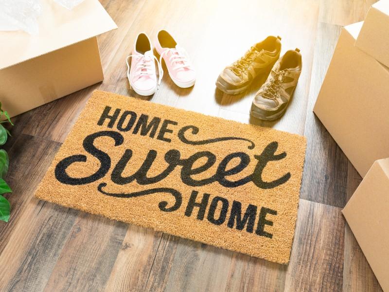 """Zerbino """"home sweet home"""" con scarpe maschili e femminili e scatole di trasloco"""