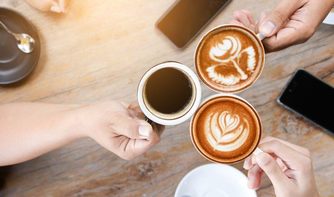 Tre mani femminili con tre diversi caffè