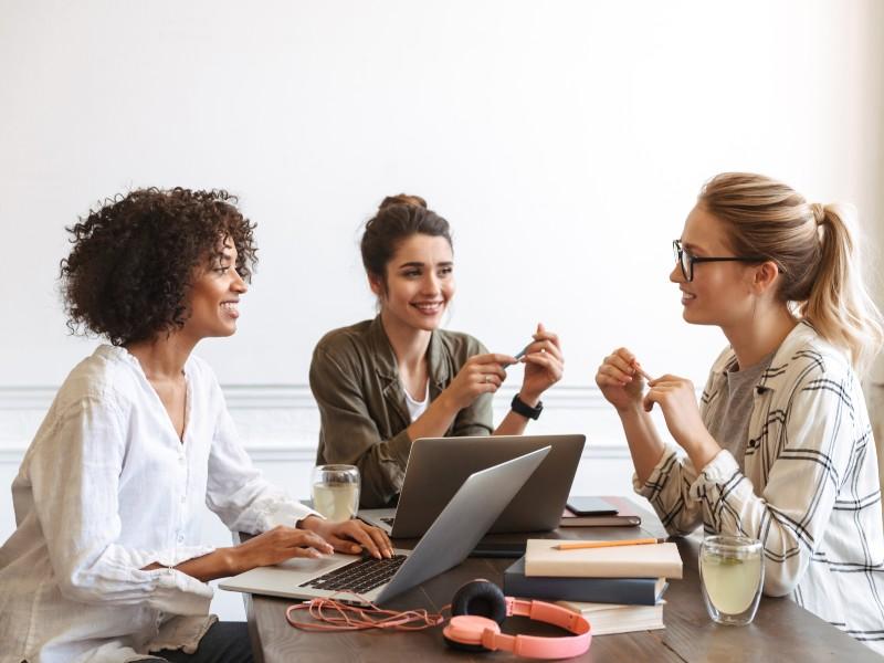 Tre giovani donne parlano sedute ad un tavolino di un bar