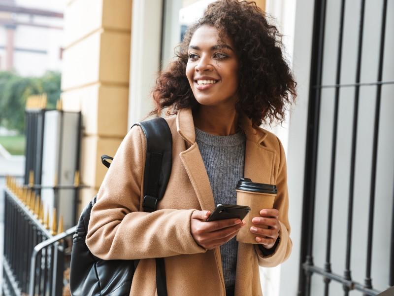 Una giovane donna passeggia con in mano un caffè e lo smartphone