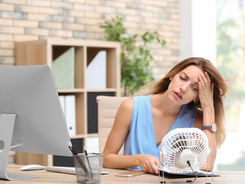 Ragazza davanti al ventilatore per vampate di calore