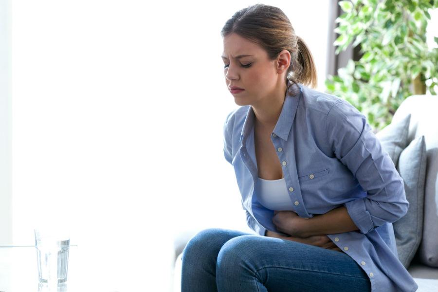 ragazza con dolori mestruali e ciclo in ritardo si tiene la pancia