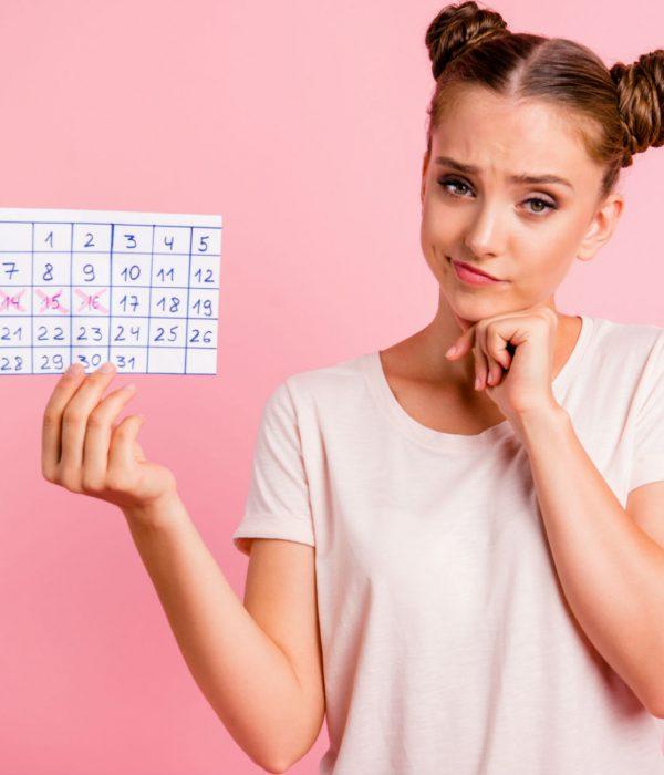 ragazza con sguardo corrucciato mostra calendario che indica le date in cui non ha avuto le mestruazioni