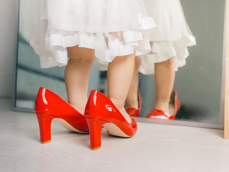 Una bambina prova allo specchio le scarpe (grandi) della mamma