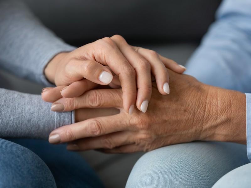 Le mani intrecciate di mamma e figlia