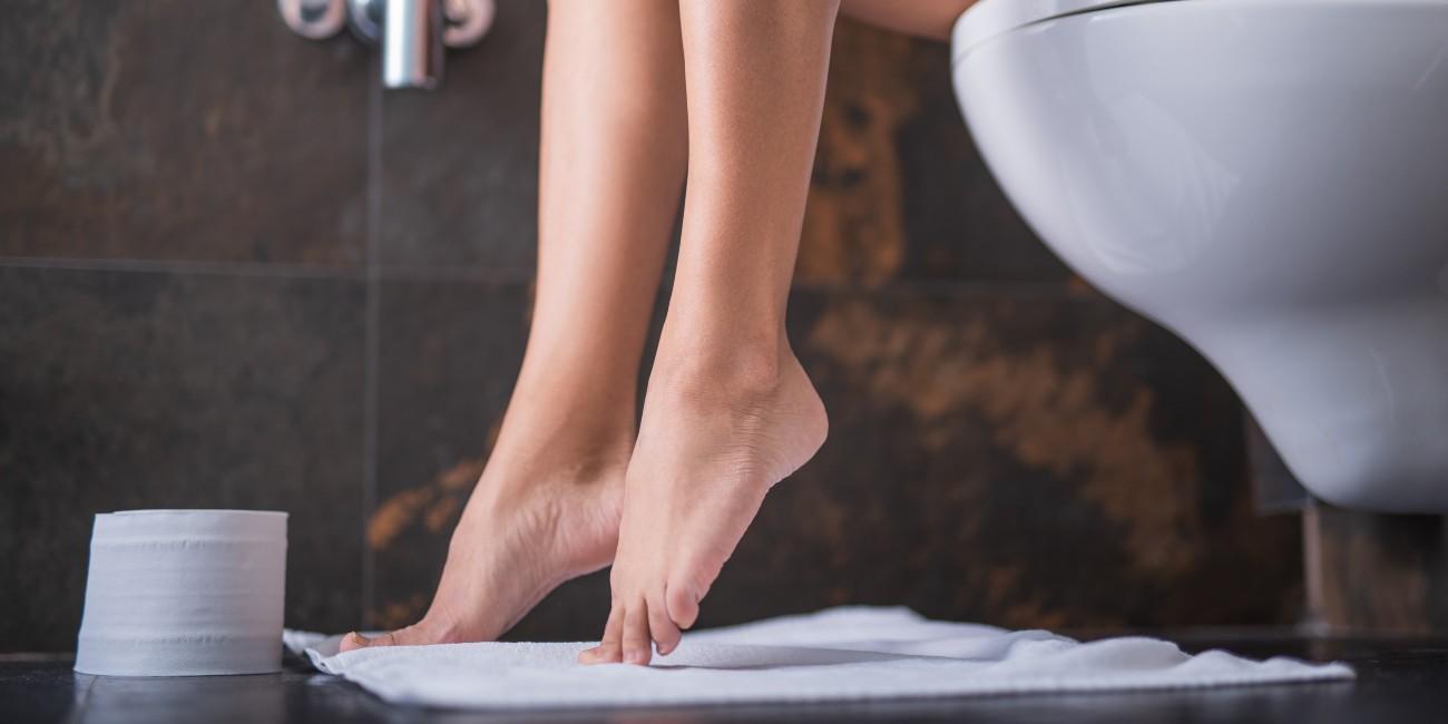 close up gambe di donna seduta sul water