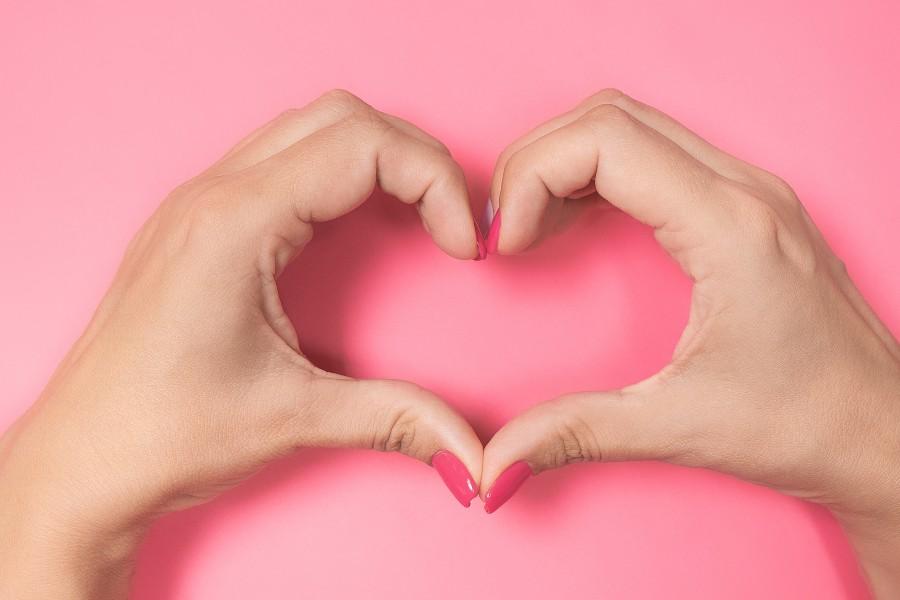 Dita femminili di due mani a formare un cuore