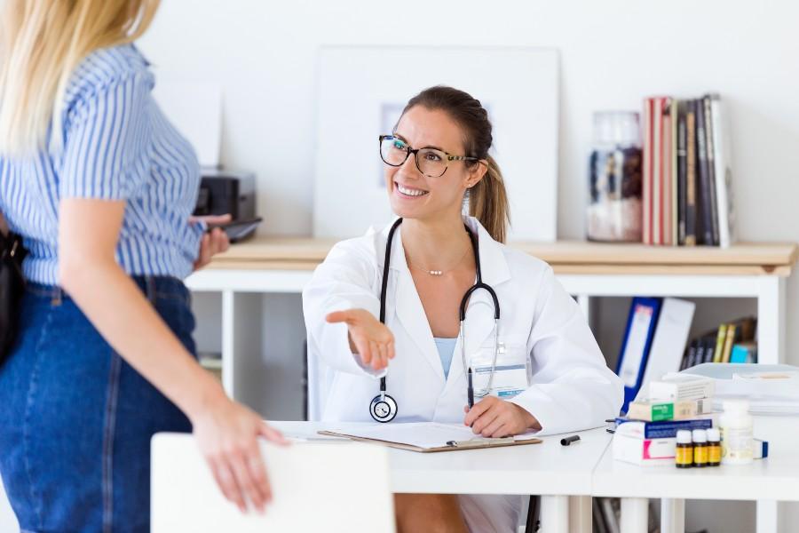 Dottoressa fa segno di accomodarsi ad una paziente