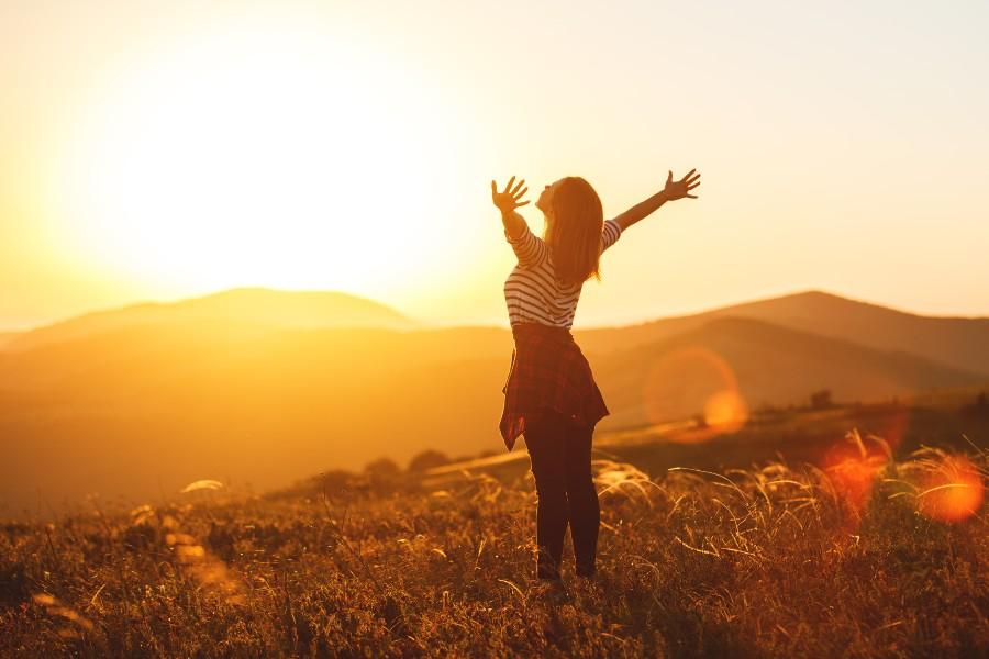 ragazza apre le braccia verso il sole