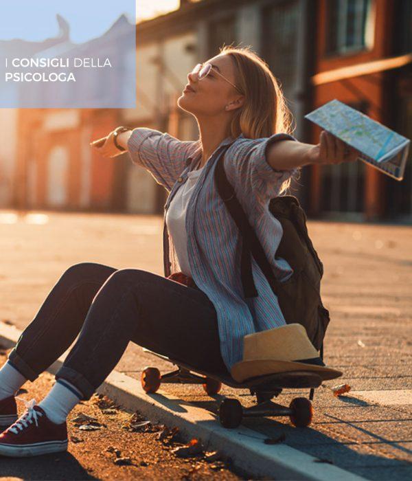 Una ragazza allarga le braccia al sole seduta su uno skateboard