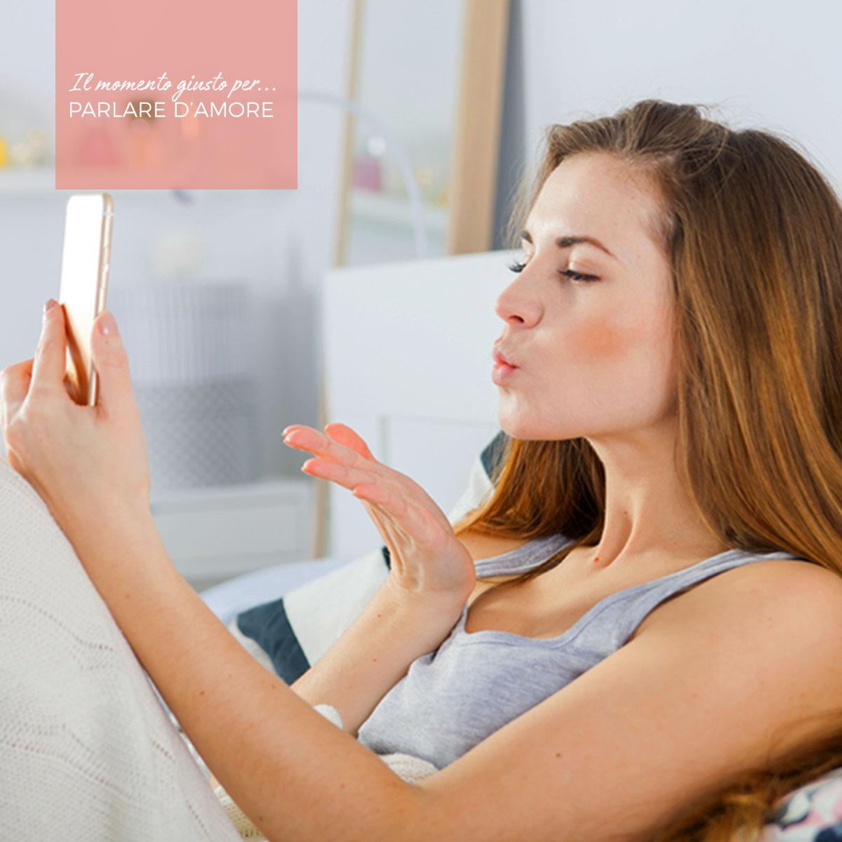 Una ragazza manda un bacio tramite videochiamata su smartphone
