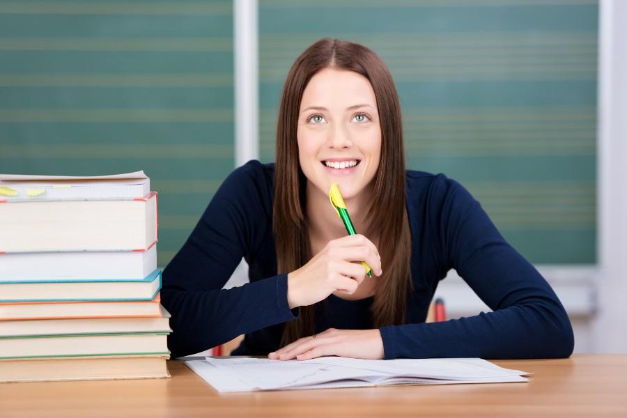 Come scegliere l'università: ragazza pensa sorridente sui libri