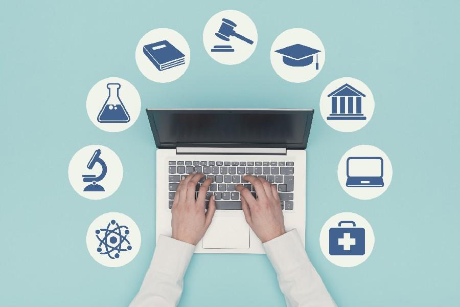 Come scegliere l'università: computer con attorno icone delle facoltà