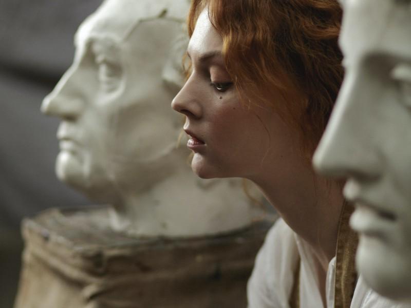 Filofobia: ragazza seduta tra due statue di marmo maschili