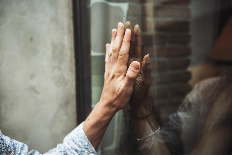 Una mano di donna poggia sul vetro di una finestra