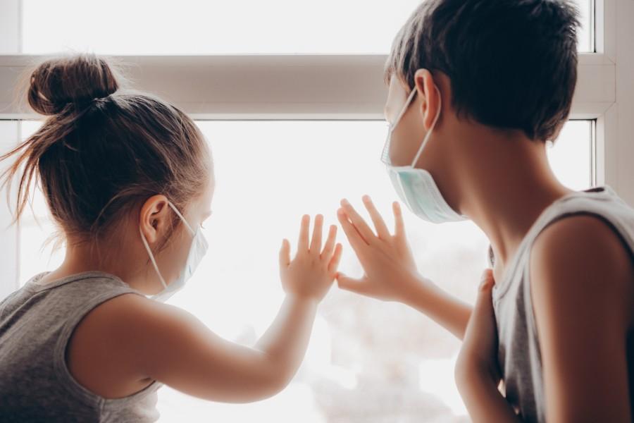 Due bambini con mascherina guardano fuori dalla finestra appoggiando la mano al vetro