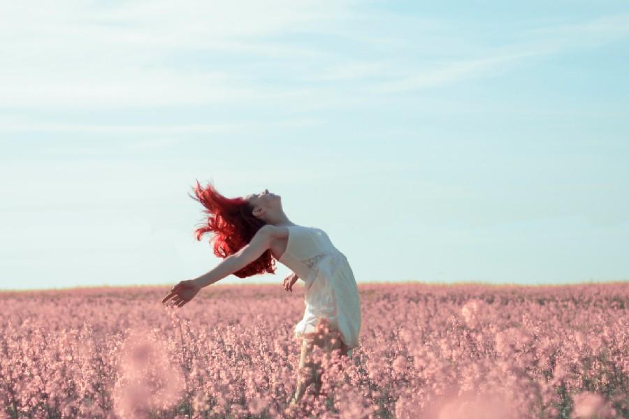 Giovane donna apre le braccia in segno di libertà