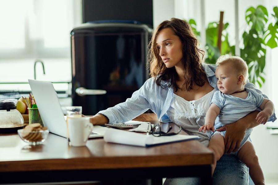 Giovane donna con bambino in braccio mentre lavora al pc