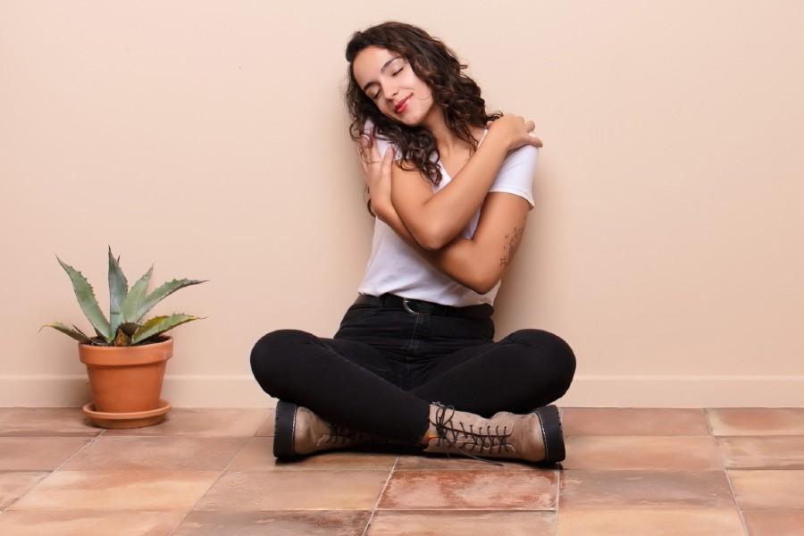 Single e felice: nell'immagine una ragazza si abbraccia da sola