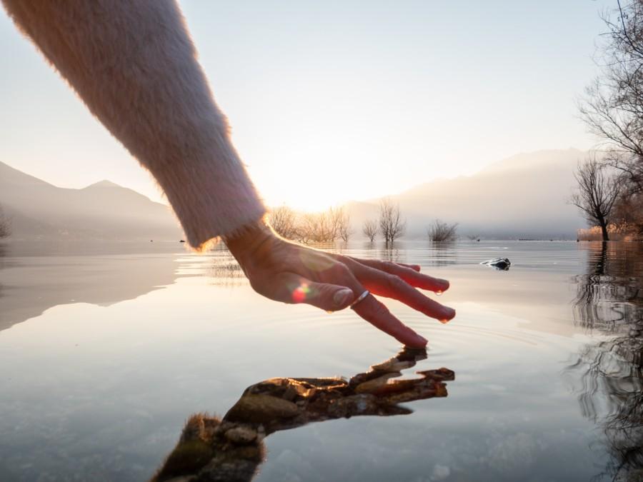 Dita femminili sfiorano la superficie di un lago