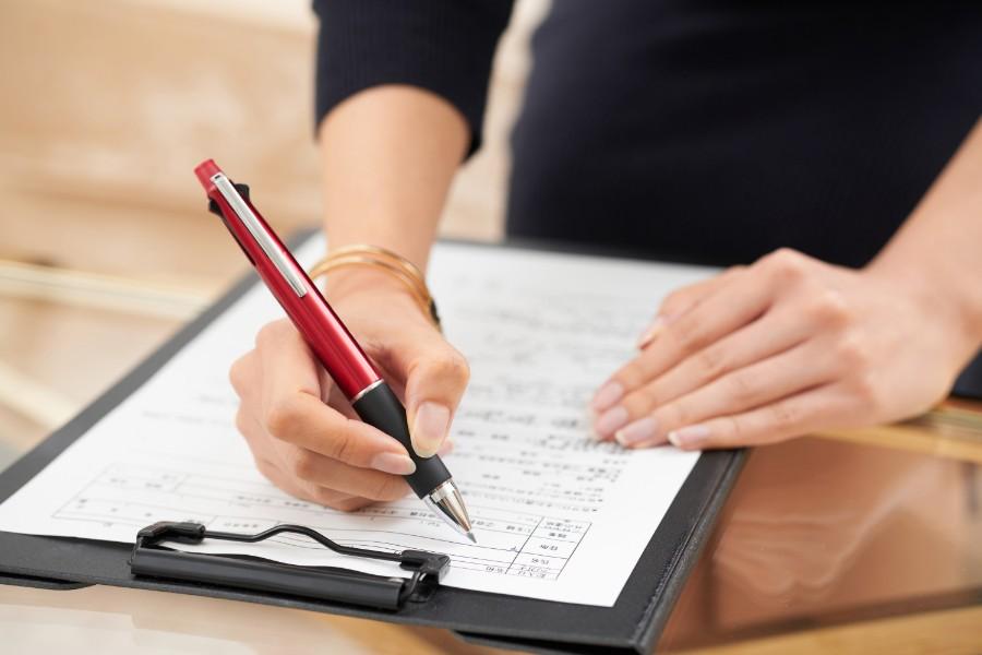 primo piano di mano femminile che compila un form per un colloquio di lavoro