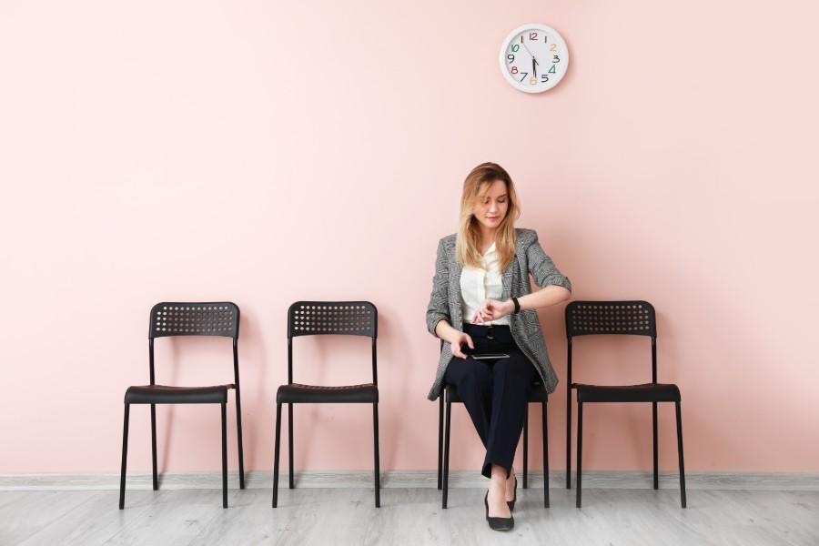 Giovane donna in attesa di un colloquio di lavoro, guarda l'orologio