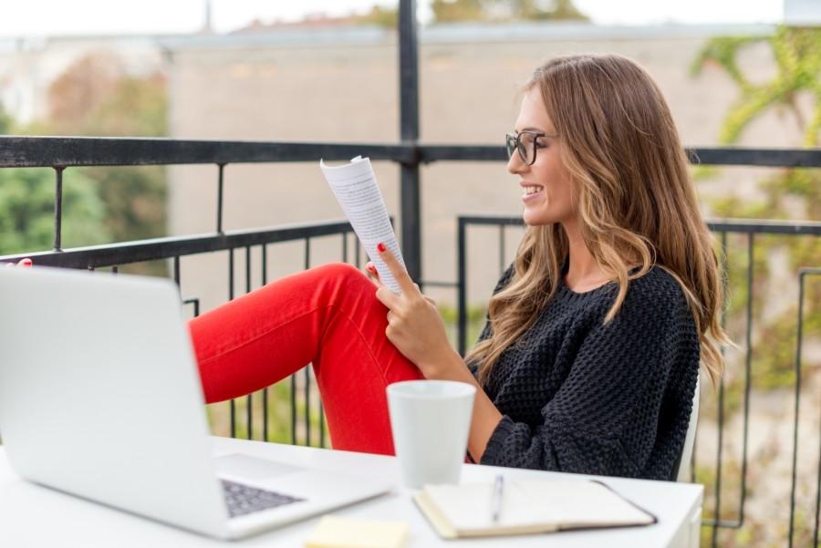 Ragazza studia sul balcone per prepararsi a un esame univesitario