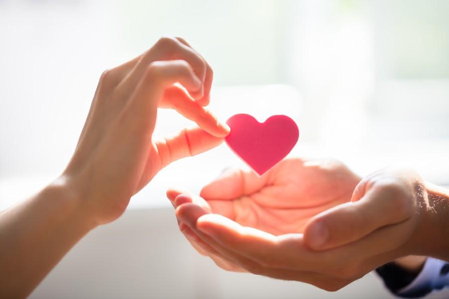 Donna porge un cuore di carta sulla mano di un uomo