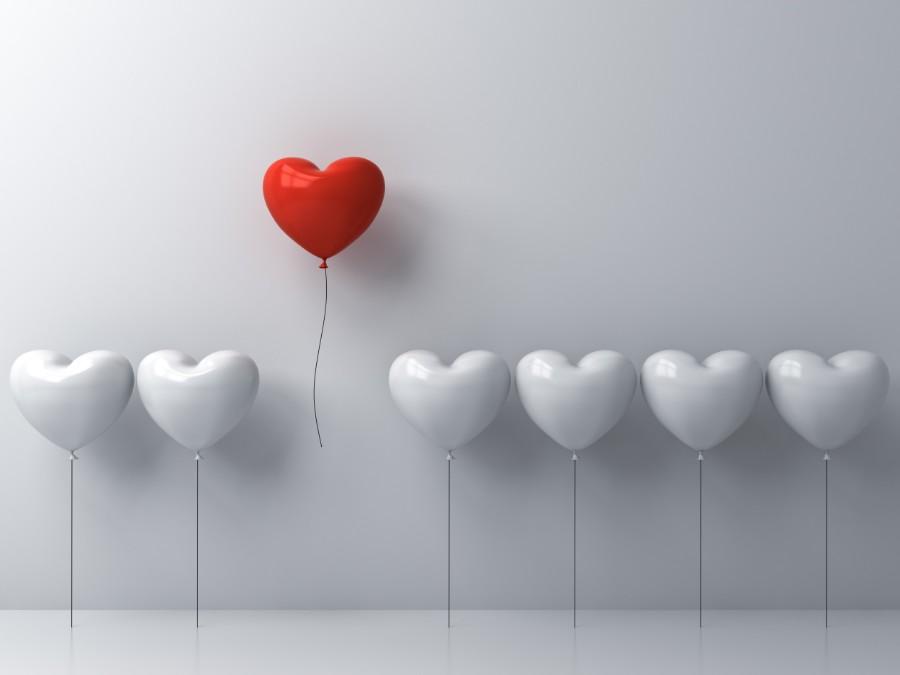 palloncino rosso a forma di cuore accanto a tanti palloncini bianchi