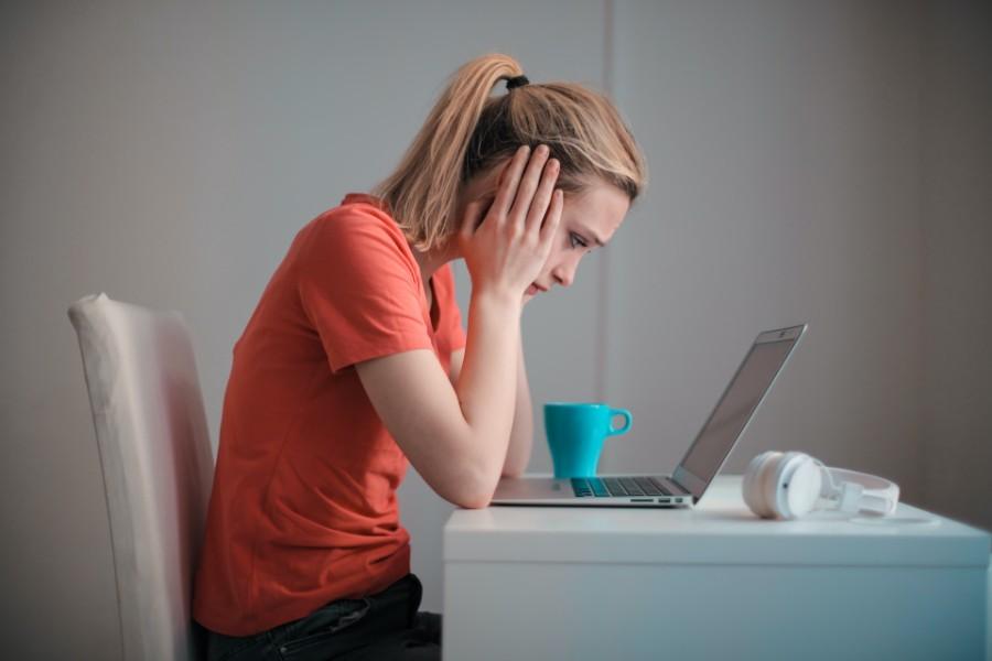 Una ragazza guarda sconfortata il computer portatile