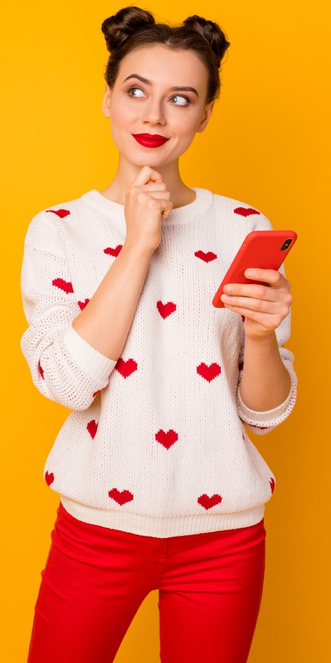 Ragazza sorridente decide chi seguire su Instagram con telefono in mano