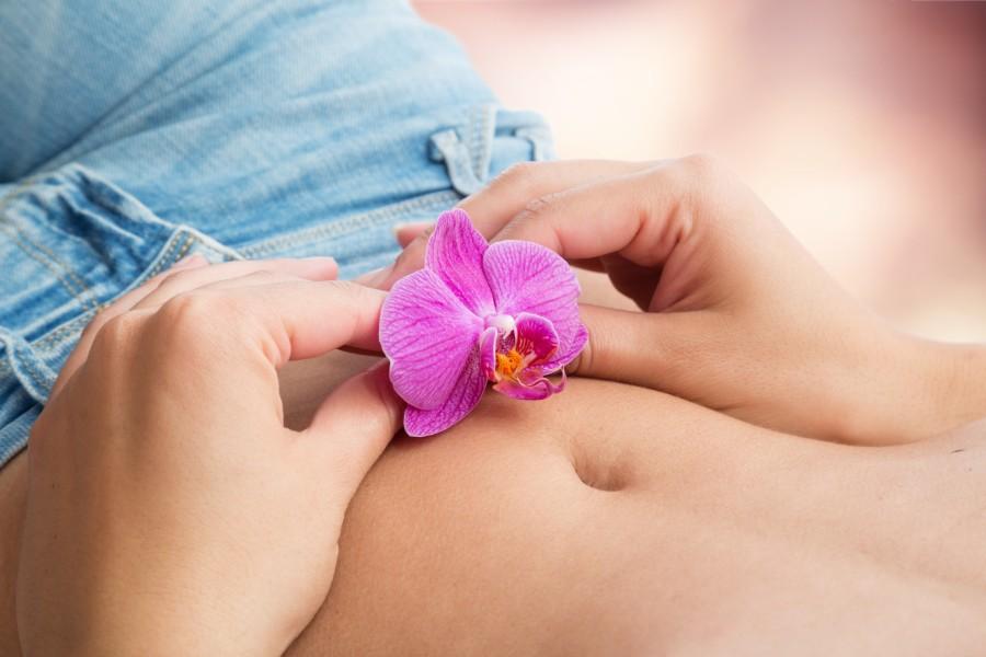 Una ragazza tiene sulla pancia un fiore di orchidea
