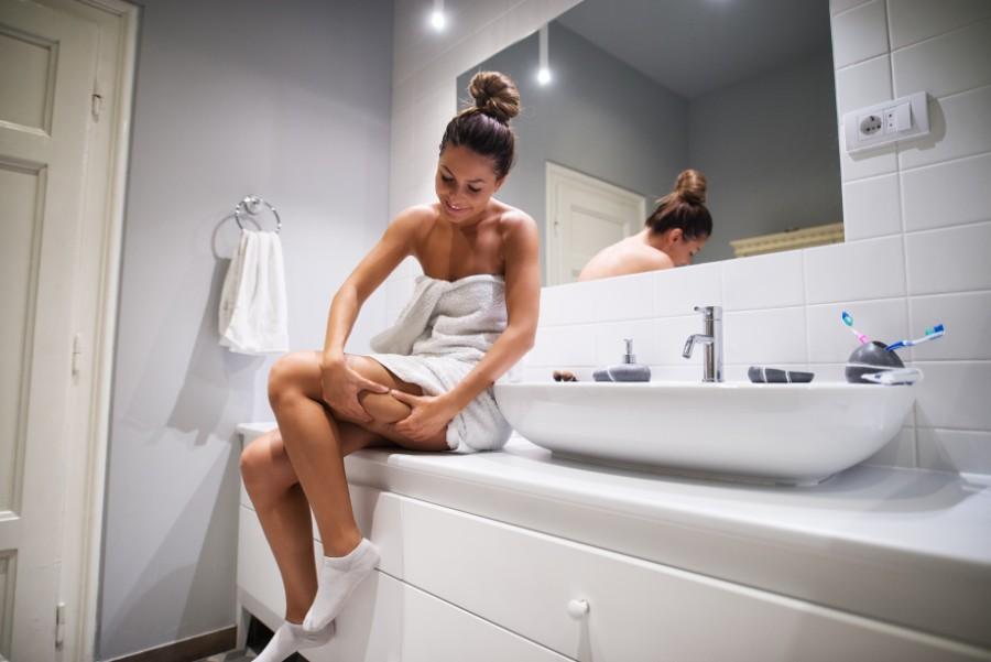 Rimedi contro la cellulite: una ragazza guarda le sue gambe