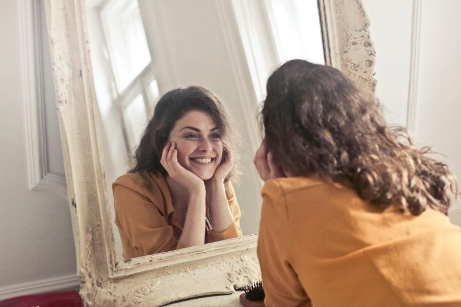 ragazza si guarda sorridente allo specchio