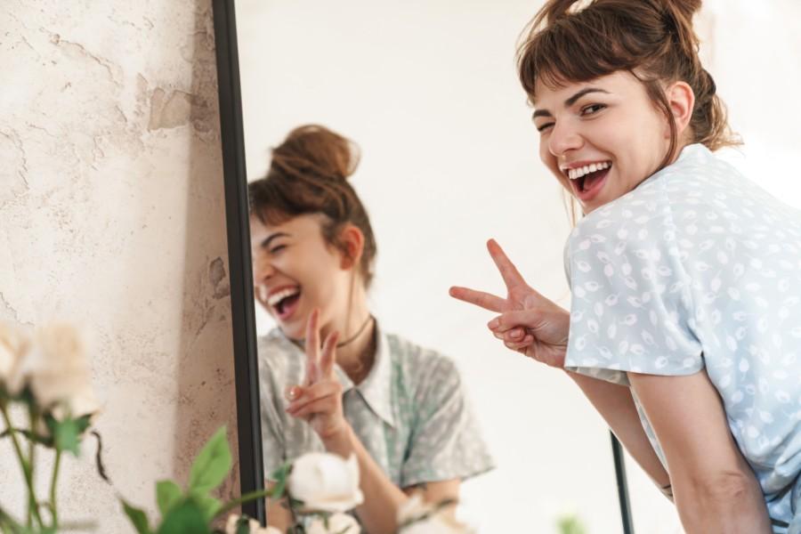 Chirurgia estetica su pazienti giovani: ragazza sorride allo specchio