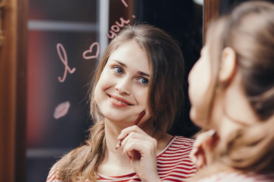 Come aumentare l'autostima: ragazza si guarda allo specchio felice