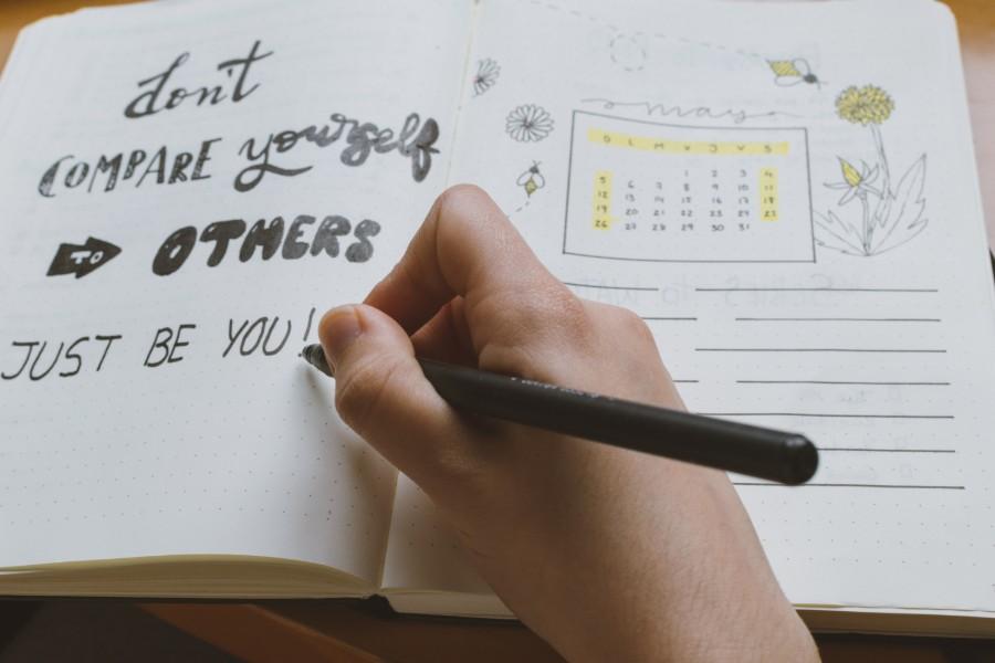Come aumentare l'autostima: mano con penna scrive su diario