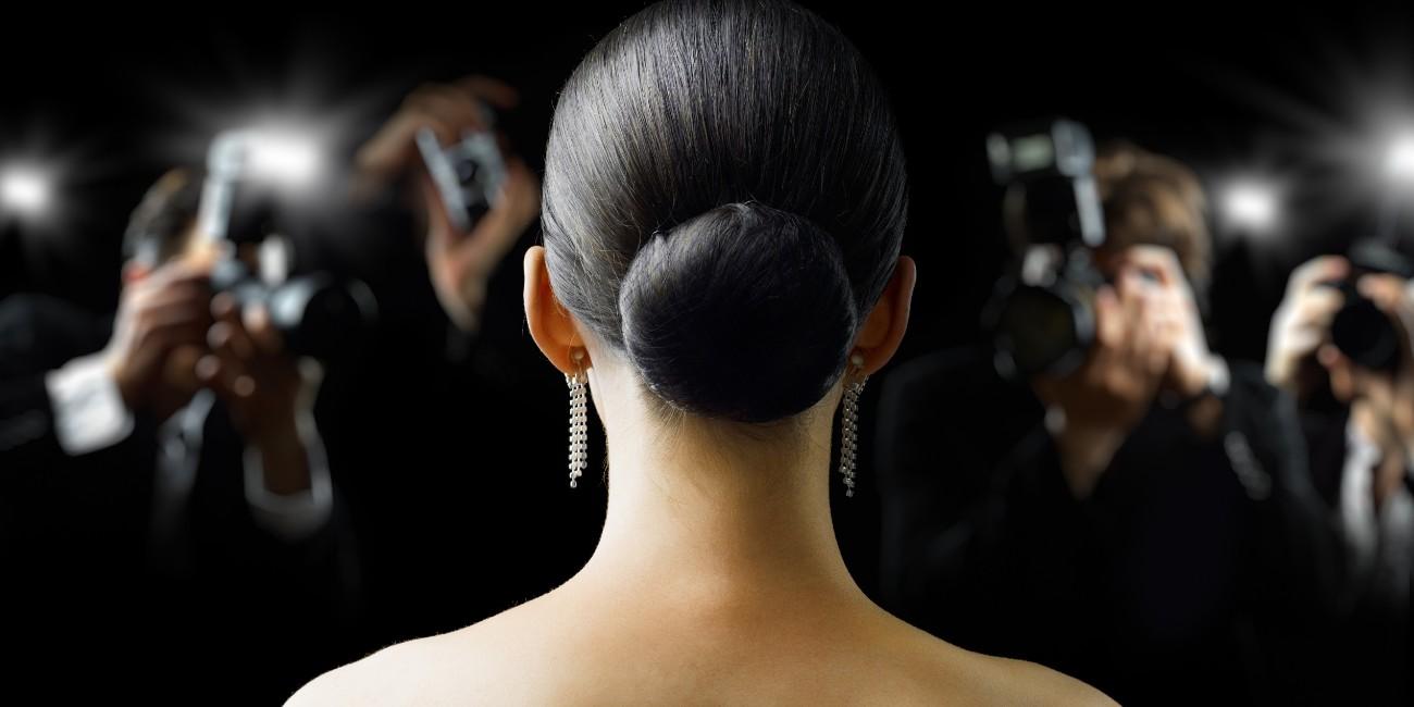 Un'attrice di spalle e fotografi