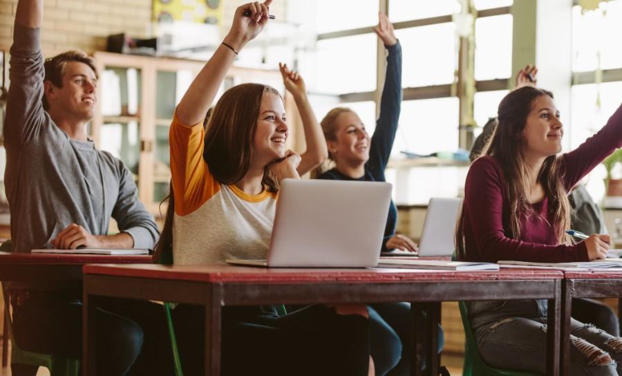Ragazzi tra i banchi di scuola con le mani alzate