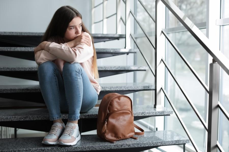Ragazza pensierosa seduta sulle scale della scuola