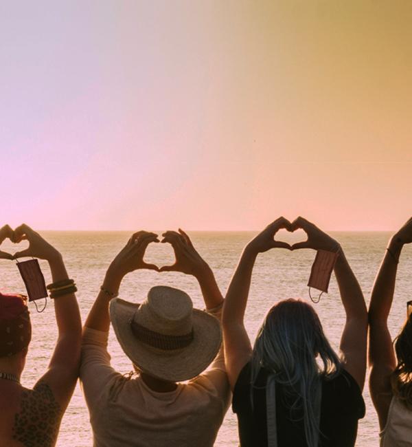 Donne riprese di spalle formano un cuore con le mani per partecipare alla challenge #SORRIDOCOLCUORE