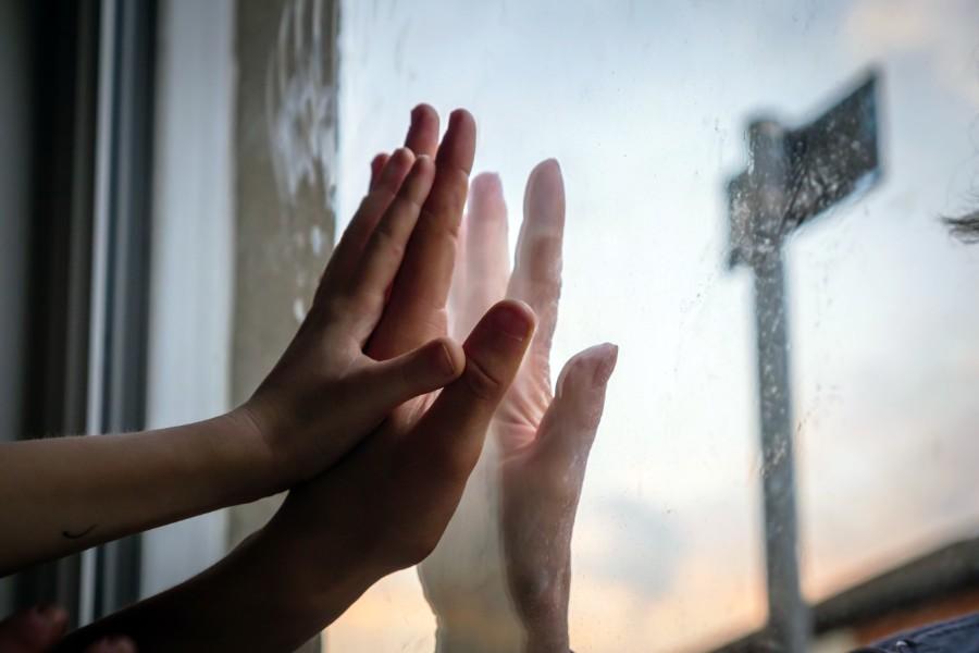 Mani si toccano attraverso un vetro