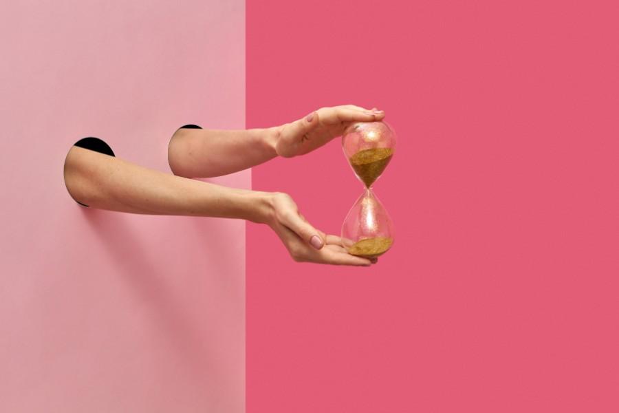 Mani di donna tengono una clessidra