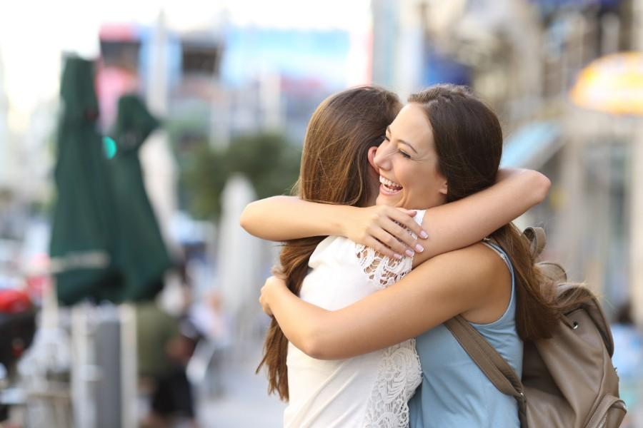 Due giovani donne si abbracciano felici
