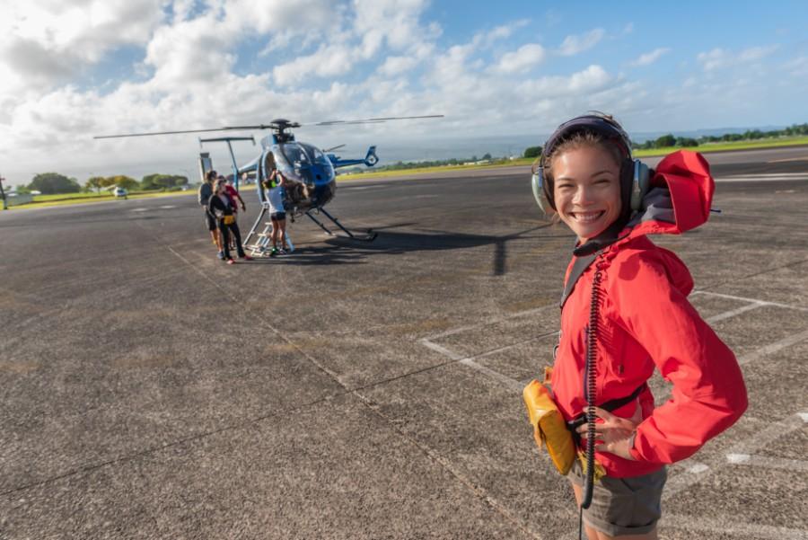 Una ragazza posa sorridente di fronte a un elicottero