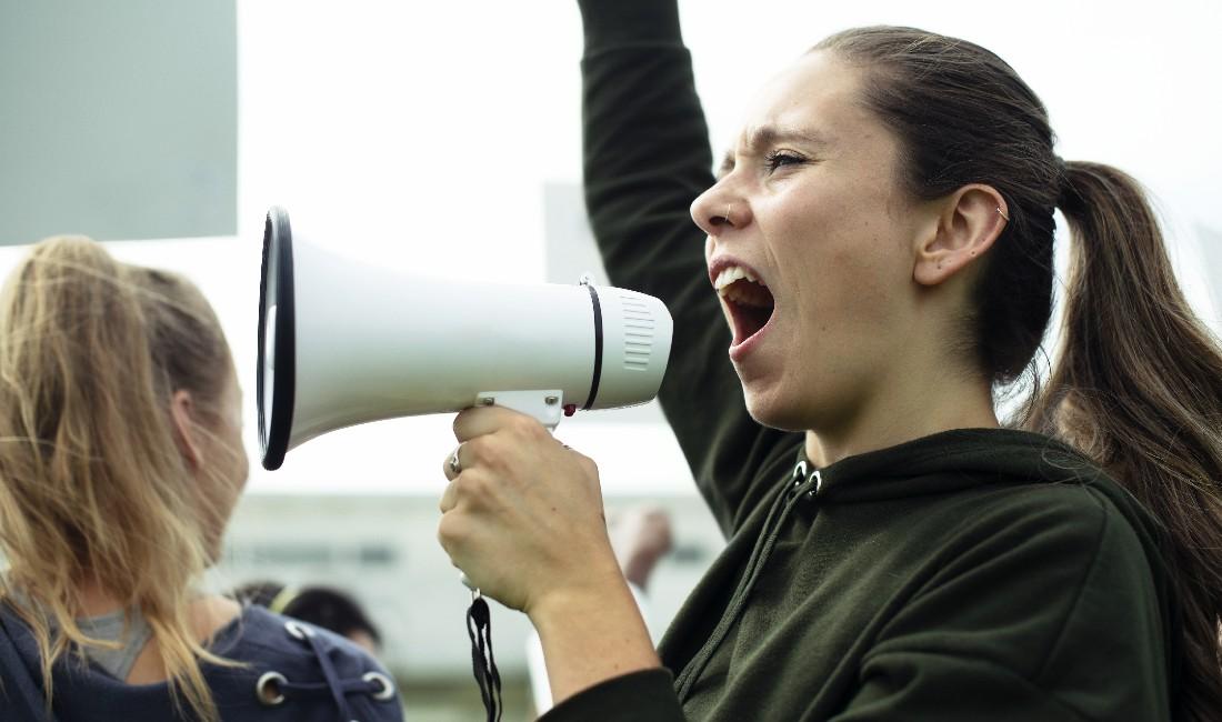 Ragazza con megafono manifesta per i diritti delle donne.