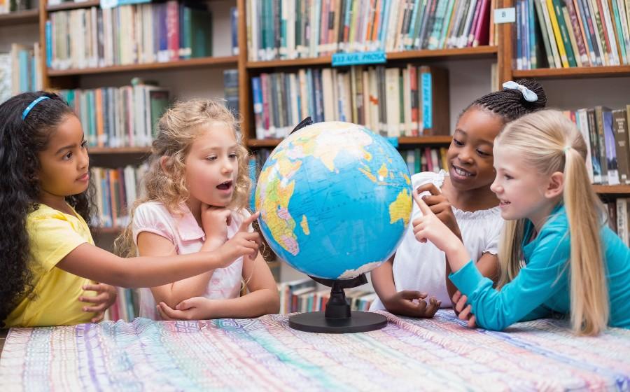 I diritti delle donne sono rispettati in tutto il mondo? Bambine guardano un mappamondo.